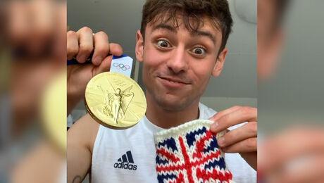 Tom Daley breit een houder om zijn gouden medaille